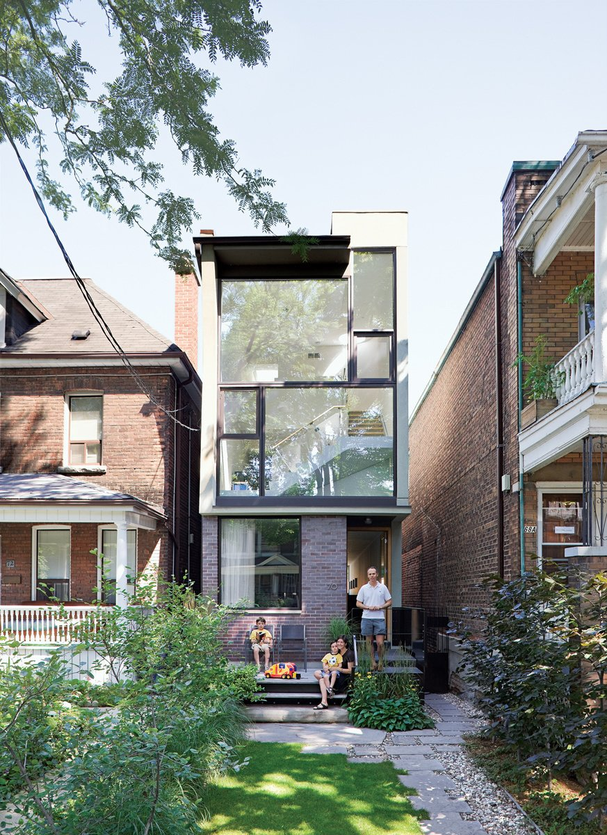 Karen White, David MacNaughtan, and their sons, Griffin and Finlay, hang out on the front deckof their narrow home in Toronto's leafy Roncesvalles neighborhood. A narrow modernist composition of glass panes and purple brick, the house slips like a bookmark between two older buildings, a bright three-story abode on a lot narrower than most suburban driveways.  Photo by Dean Kaufman. Read more about the small house here. Tagged: Outdoor, Grass, Pavers Patio, Porch, Deck, and Small Patio, Porch, Deck.  Curb Appeal: 7 Stunning Facades That Must Look Great on Google Maps by William Harrison from Innovative Urban Homes