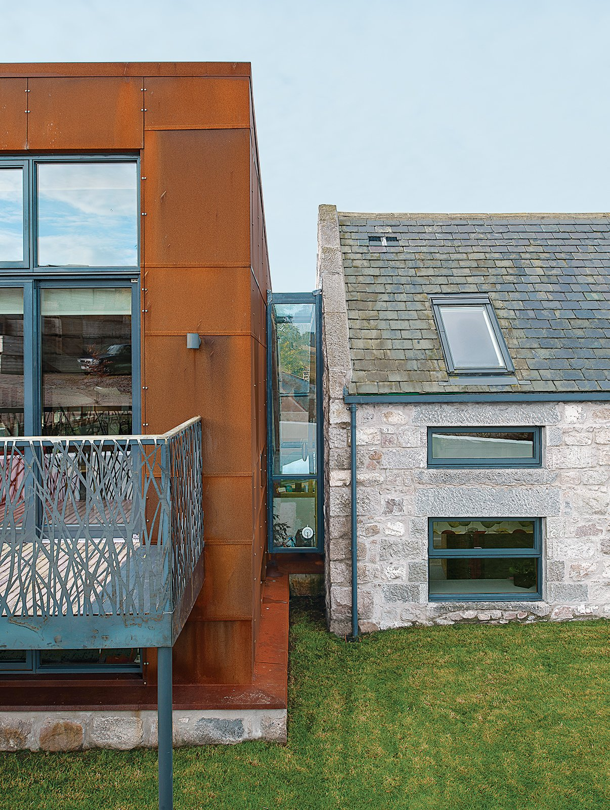 """Cor-Ten steel from a ship building yard clads the new structure, which connects via a glass """"bridge"""" to a rebuilt stone farmhouse containing the bedrooms.  Photo 14 of 16 in 15 Modern Additions to Traditional Homes from This Farmhouse is a Cor-Ten Steel-Clad Dream"""