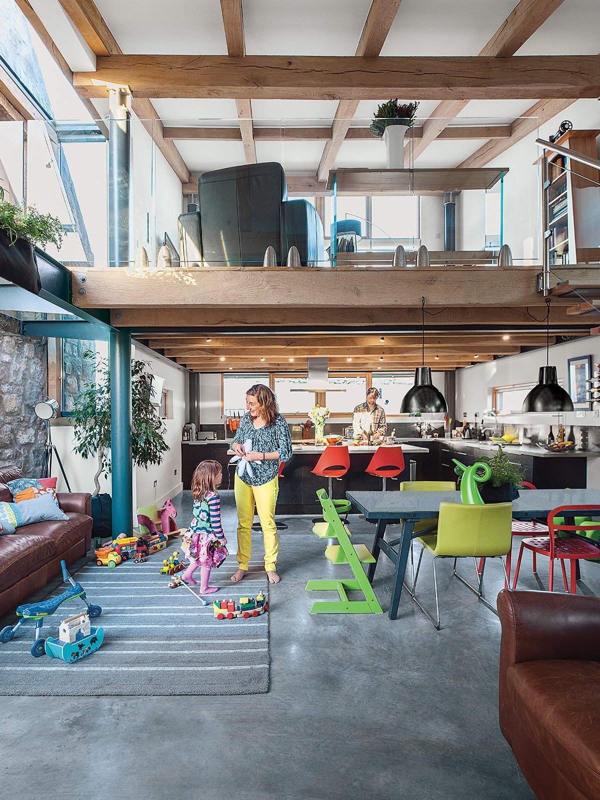The bottom floor contains the kitchen and the dining area; the lounge is upstairs. The cabinets are from Ikea, as are the table and chairs, and the child's Tripp Trapp chair is from Stokke.  Colorful and Vibrant Farmhouses by Luke Hopping from This Farmhouse is a Cor-Ten Steel-Clad Dream