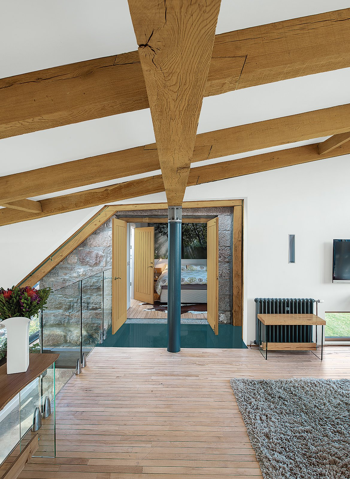 Reclaimed oak beams dominate the upstairs lounge, which leads to the guest bedroom. Tagged: Living Room and Light Hardwood Floor.  Photo 9 of 11 in This Farmhouse is a Cor-Ten Steel-Clad Dream