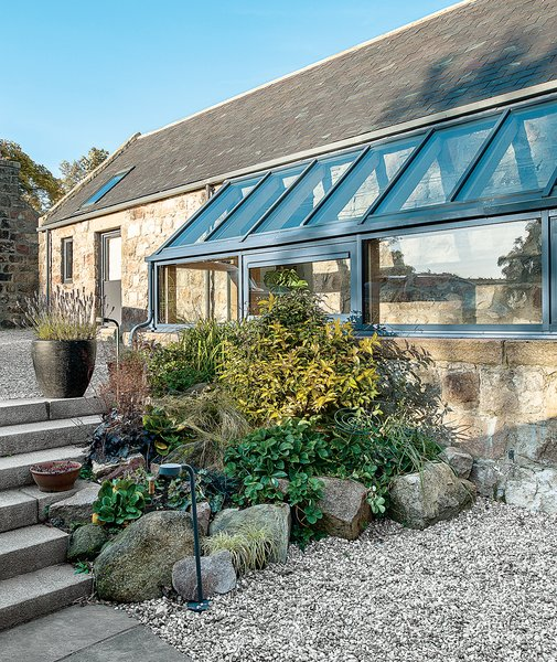 The glass balustrade and floor were sourced in Germany and installed by James Aiken. Angelique, the founder of Papillon Designs and Landscaping, clustered plantings around the exterior glass addition.