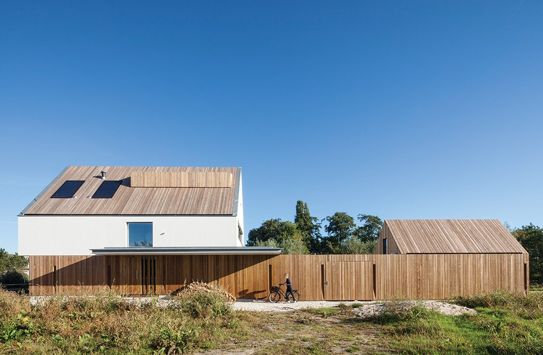 With its vertical wood slats, the garden fence helps unify the main house and the smaller shed. Tagged: Exterior, House, and Wood Siding Material.  Photo 3 of 13 in A Modern Take on the Pitched-Roof