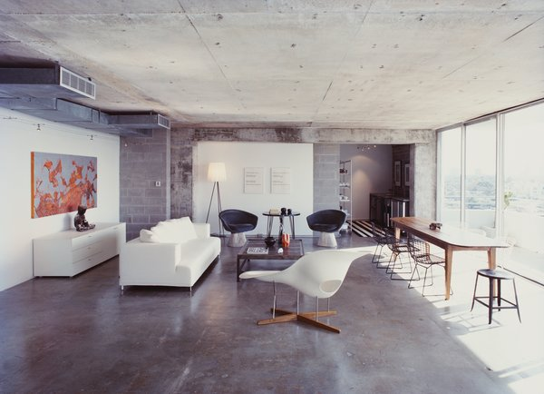 A Philippe Starck standing lamp and an Eames chaise longue bracket the living room; two Lawrence Weiner prints hang behind a pair of Warren Platner chairs and a table purchased from a River Oaks estate sale; at far left of the room, a partial wall of new cinderblocks hides a return air vent.