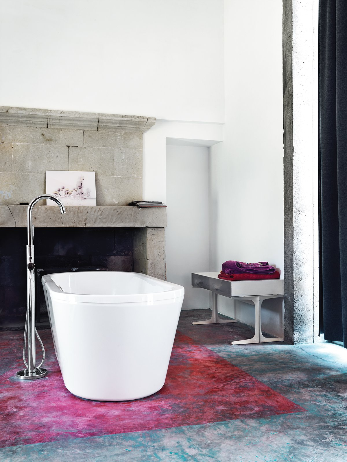In the master bathroom, the floor's subtle resin treatment was initially painted on the concrete as full-on orange, but started peeling immediately. Monory scrubbed it off until only a wash of the hue was visible. The bench is from Ikea.  Photo 5 of 12 in Matali Crasset Renovates Monory Farmhouse