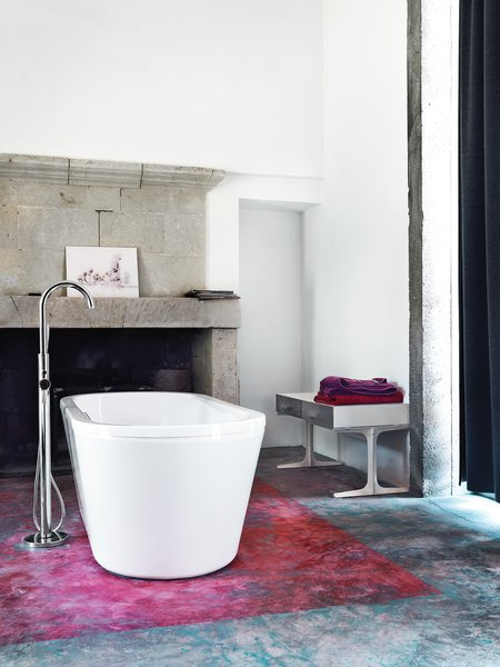 In the master bathroom, the floor's subtle resin treatment was initially painted on the concrete as full-on orange, but started peeling immediately. Monory scrubbed it off until only a wash of the hue was visible. The bench is from Ikea.