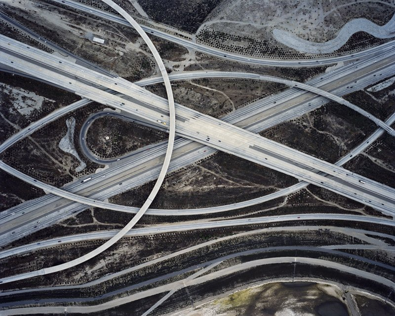 A freeway interchange in Southern California casts sweeping arcs over the terrain. Photo by Christoph Gielen.