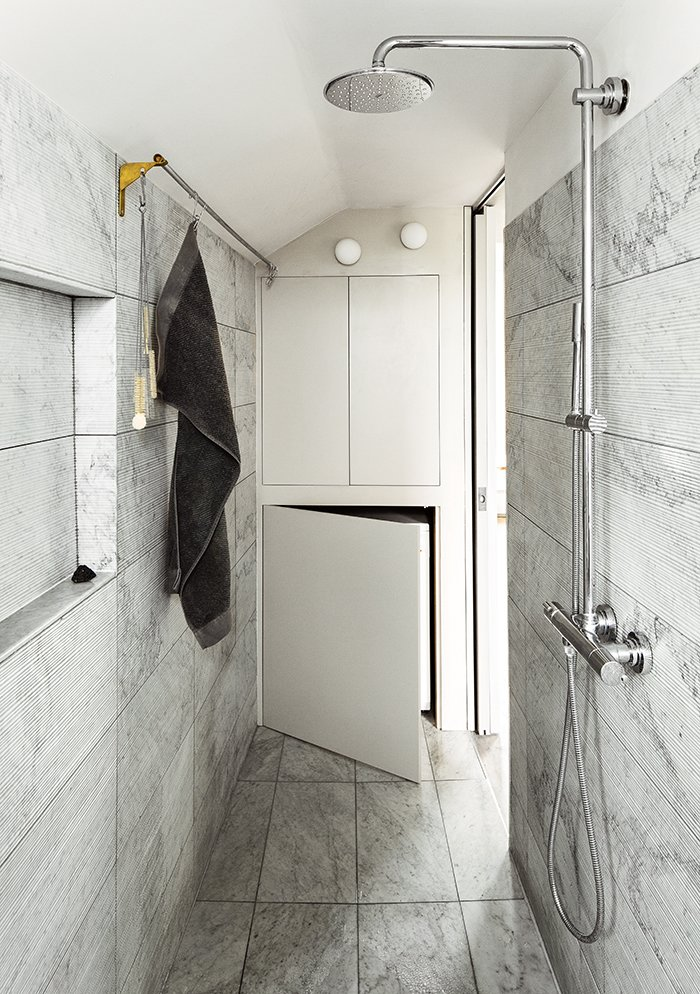 The Salvatori marble tiles in the bathroom were added at the last minute, once everyone was confident that they would not put the project over budget. Tagged: Bath Room, Full Shower, Enclosed Shower, Wall Lighting, Marble Wall, and Marble Floor.  Photo 5 of 10 in This Is How You Can Live Large in a Small Space