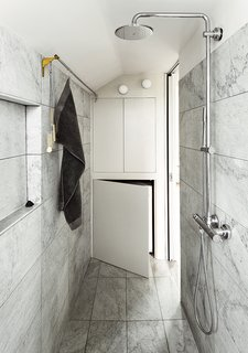 Discover 9 Modern Ways to Use Marble in Your Bathroom - Photo 8 of 9 - In a London apartment that measures less than 400 square feet, a small bathroom didn't have to mean that the space would be short on design or elegance. By using a textured-marble tile, Ullmayer Sylvester Architects and Rogeroger Design Solutions elevated the narrow bathroom and took advantage of built-in storage to create a sophisticated and effectively designed room.