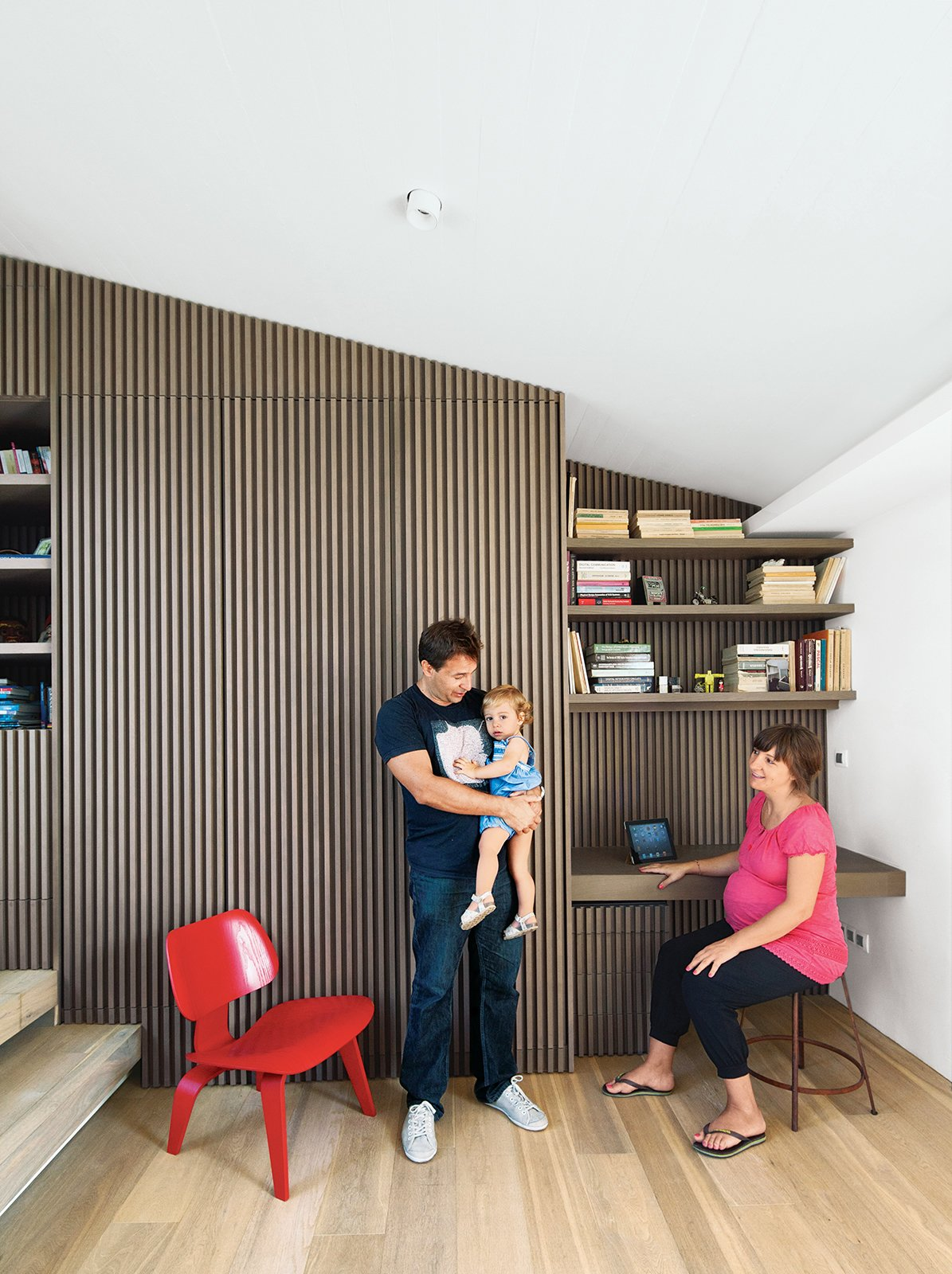 Iason Vassiliou, Maria Voutsina, and their daughter, Angeliki, relax in a landing-level office at their apartment in Athens, Greece. Tagged: Office, Chair, Desk, Shelves, and Light Hardwood Floor.  Ideal Angles by Jill Southern from Odd Angles Don't Stop This Apartment's Transformation