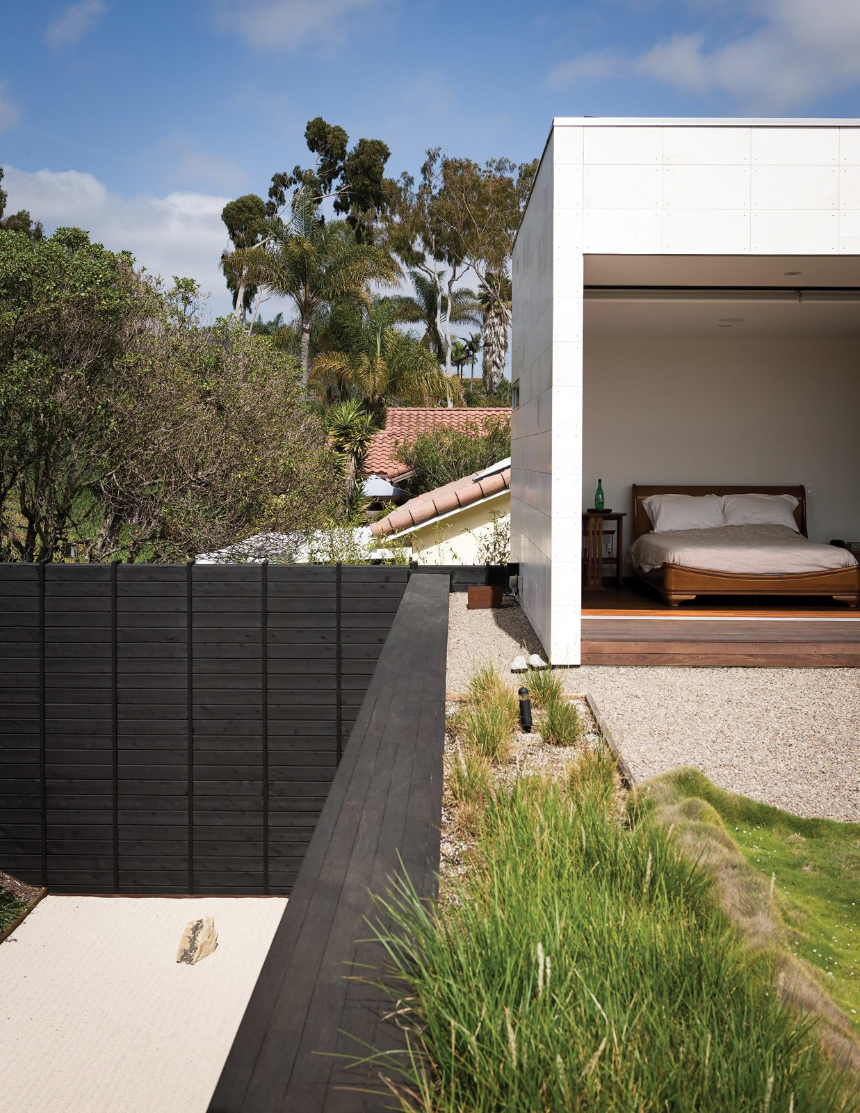 The limestone-clad volume at the east end of the house extends to the second story, housing Shino and Ken's master suite, which opens onto the planted roof deck. Tagged: Bedroom and Bed.  Bedrooms by Dwell from An Atypical Modern Home in Southern California