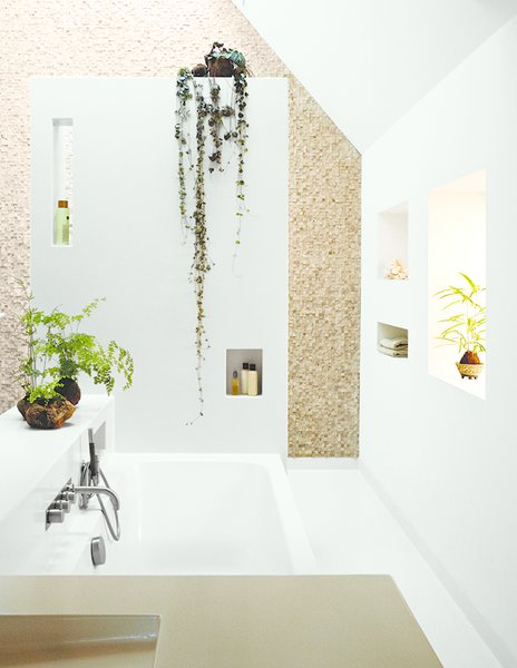 Amending Meeuwissen's early request for an open bathroom space, the architects devised a more private chamber with an overhead skylight and walls in stone tile from Intercodam Tegels.