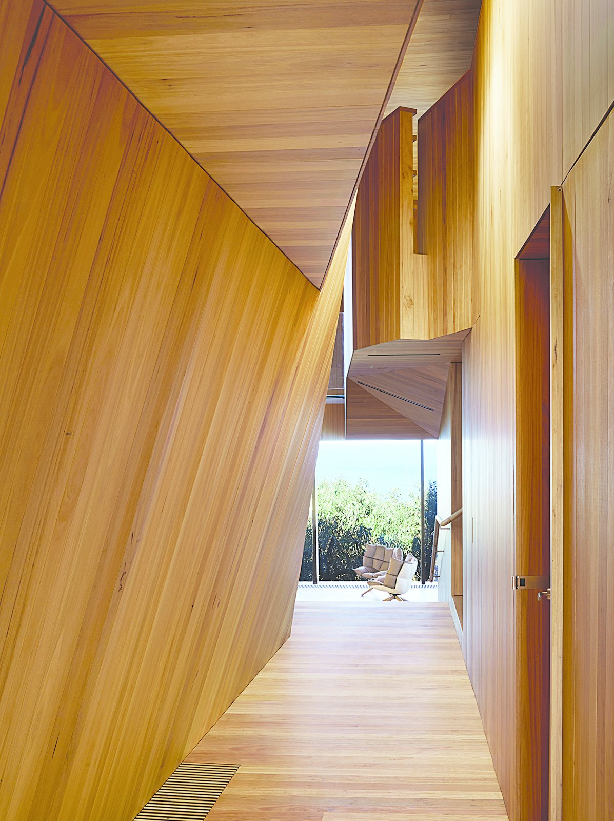 The house that architect John Wardle designed for a couple in coastal Fairhaven, Australia, twists and bends to comply with local laws that prevent buildings from disrupting the ridgeline views from the Great Ocean Road.  Photo 2 of 9 in A Eucalyptus-Lined Oceanfront Home in Australia