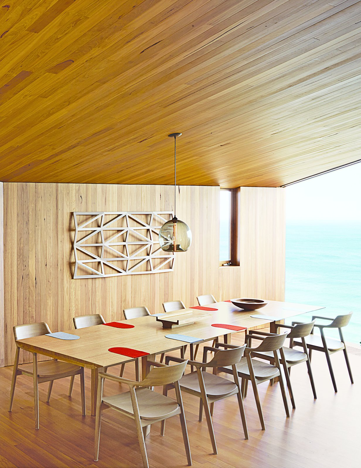 Wardle's firm also designed the dining table, where up to ten guests can gaze out at the Southern Ocean. The solid-oak Hiroshima chairs are designed by Maruni. Tagged: Dining Room, Chair, Pendant Lighting, Table, and Medium Hardwood Floor.  Photo 24 of 41 in 50 Dashing Dining Rooms from A Eucalyptus-Lined Oceanfront Home in Australia