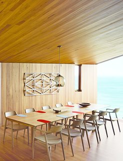 A Eucalyptus-Lined Oceanfront Home in Australia - Photo 6 of 9 - Wardle's firm also designed the dining table, where up to ten guests can gaze out at the Southern Ocean. The solid-oak Hiroshima chairs are designed by Maruni.