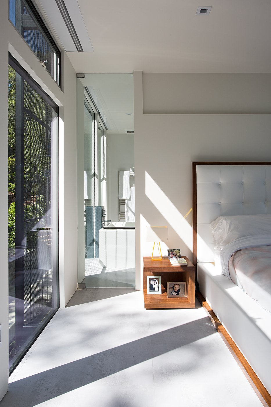 Light floods the second floor master bedroom, and floor-to-ceiling windows are buffered by adjacent steel mesh wall. A Modloft Ludlow platform bed anchors the room, and Pablo Designs bedside table lamps delicately punctuate the minimal space. Tagged: Bedroom, Ceiling Lighting, Bed, and Concrete Floor.  Bedroom by MeryamCafar from This Modern Addition in Northern California Has the Ultimate Rooftop Hangout