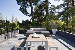 10 Modern Rooftops For Summer Relaxing and Entertaining - Photo 9 of 10 - The roof deck is a place for entertaining, and offers scenic hillside views. During the design process, the team was challenged with preserving these views while adhering to the required 3.5-foot railing height mandated by building code, a height that would block all views while seated. As a solution, the team came up with open metal railings that would maintain safety while preserving the view.