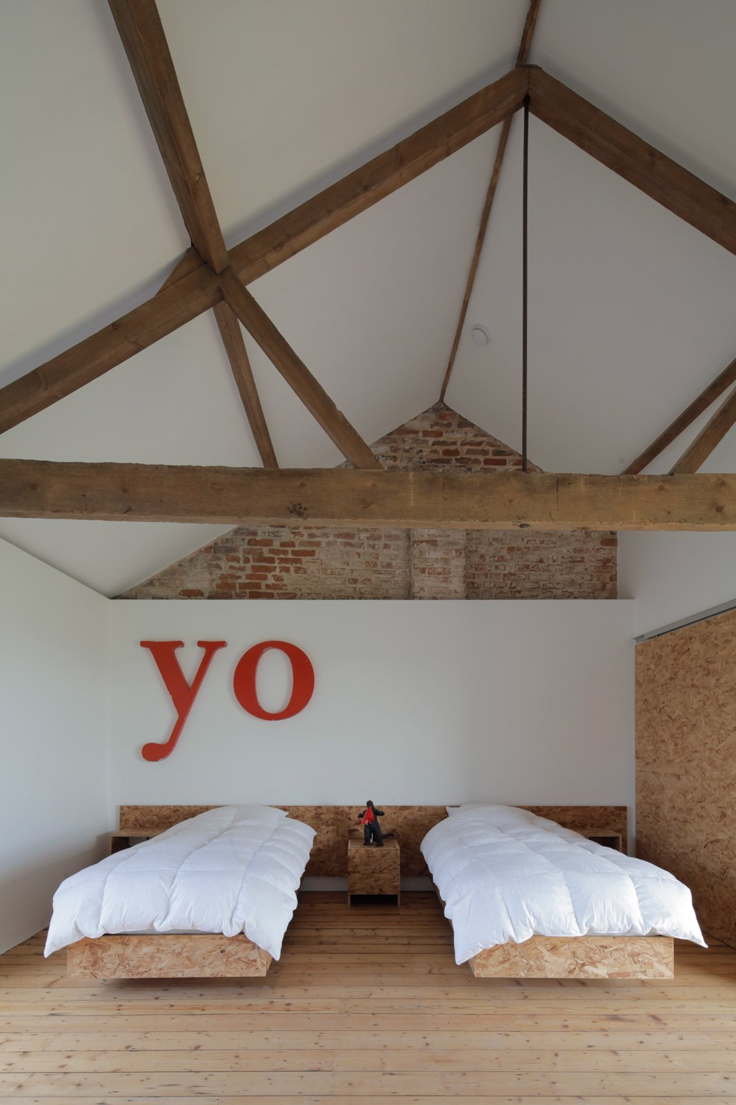A guest room in this repurposed barn in the English countryside lets the ceiling do the talking. Photo by Christoffer Rudquist. Tagged: Bedroom and Bed.  Photo 12 of 12 in A Pair of English Barns Hide Unabashedly Bold and Budget-Friendly Minimalist Interiors
