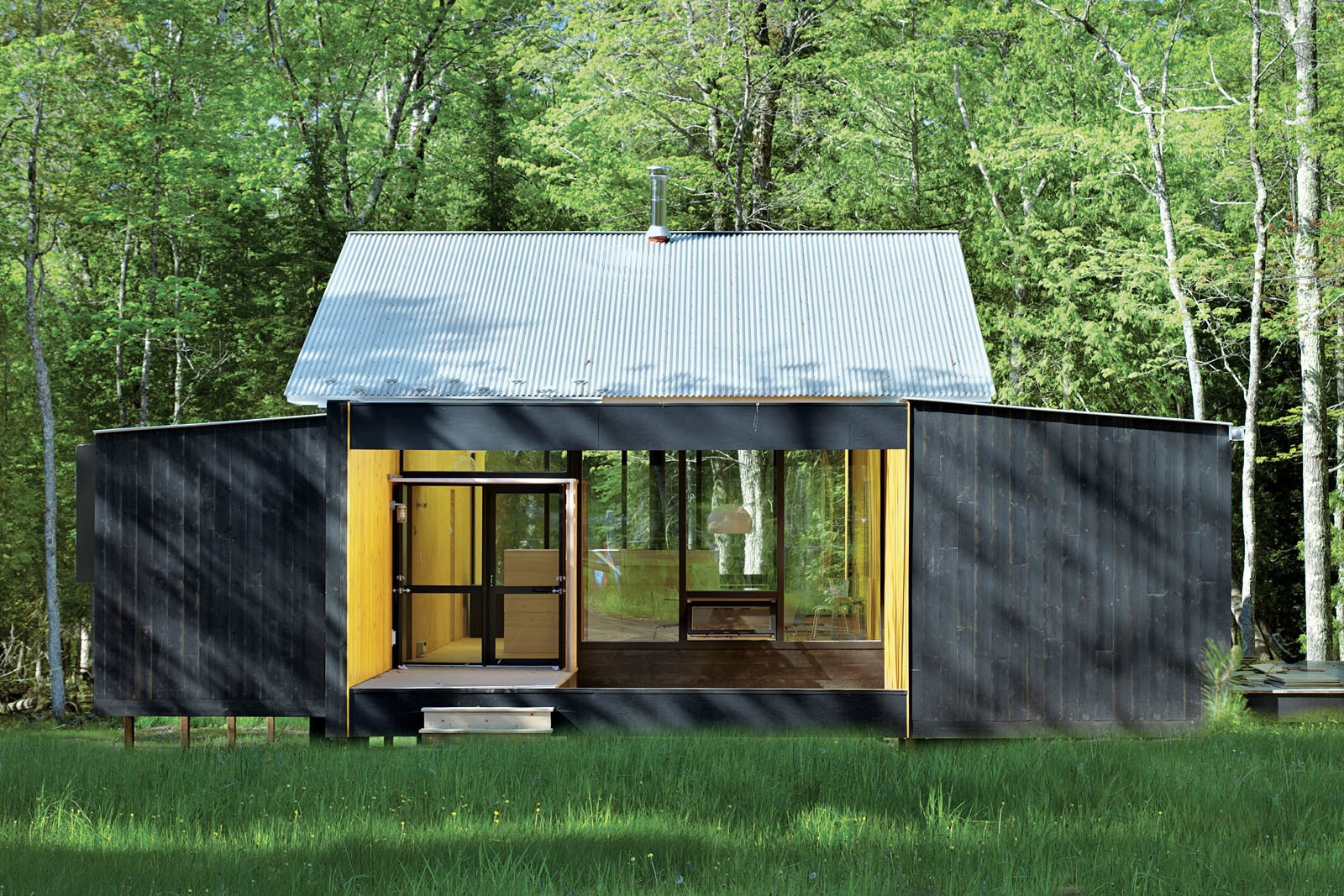 Architect Charlie Lazor opted for a wash of black on the prefab cabin he designed on Madeline Island, Wisconsin. Tagged: Exterior, Prefab Building Type, House, Cabin Building Type, Metal Roof Material, Wood Siding Material, and Glass Siding Material.  Photo 71 of 101 in 101 Best Modern Cabins from Small Homes in the Midwest