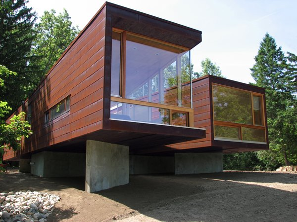 """Architect Jim Garrison of Brooklyn-based Garrison Architects was asked to design a retreat for visiting families on an idyllic lakeside expanse of land at a boarding school for troubled teens, Star Commonwealth in Albion, Michigan. To drastically reduce academic interruption and cut site noise, Garrison decided early on to create an 1,100-square-foot modular building dubbed Koby, with two bedrooms on opposite sides of the structure and a common dining area in the middle """"as a therapeutic space for families to gather and eat together."""""""