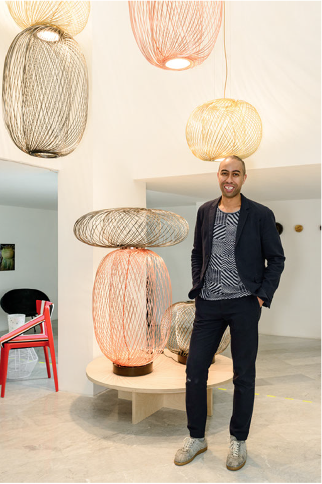 Burks, standing with his Anwar LED lighting collection for Parachilna, at his Dwell-hosted Man Made exhibition in Milan.