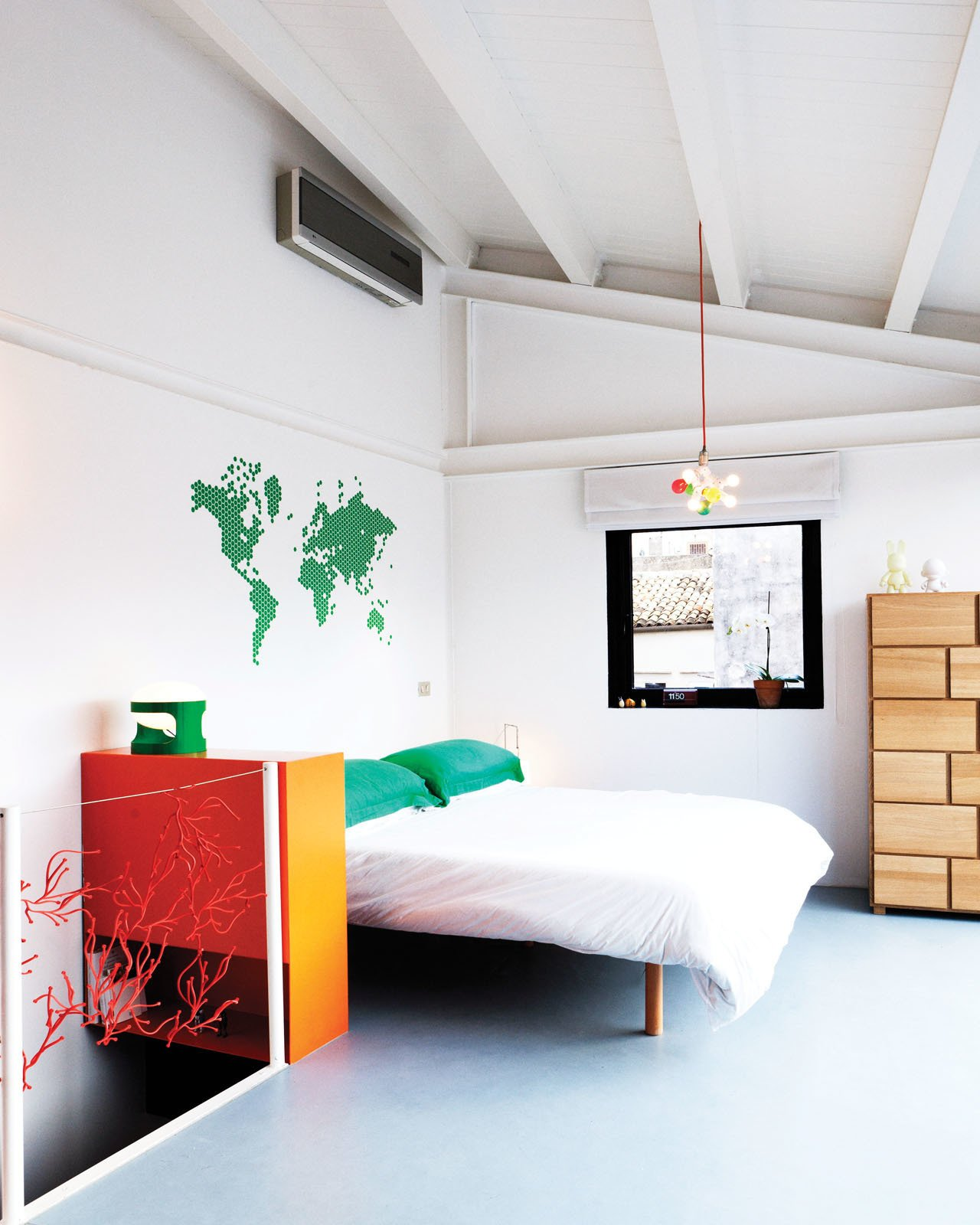 Francesco and Mafalda's bedroom is open and playful with only a bit of Algue by Ronan and Erwan Bouroullec guarding the stairs. The lamp was designed by Francesco himself and the decal on the wall is from My Vinilo. Tagged: Bedroom, Bed, Dresser, and Pendant Lighting.  How to Design With Maps by Zachary Edelson from Stylish Sicilian Bedroom