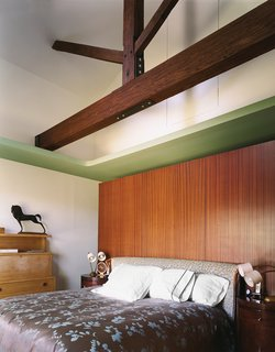 At Home in a Modern Church - Photo 7 of 9 - The Suarezes opted for a cozy bedroom with beautiful details, old and new—lustrous mahogany behind the bed, Baker tables beside it. The long beam overhead replaced the original, but smaller beams above it are authentic.