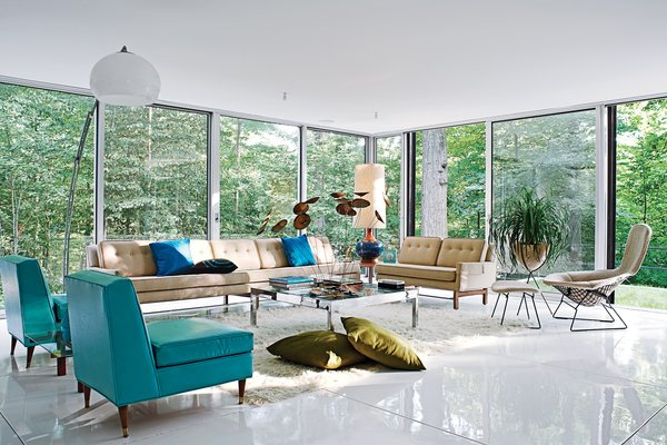The living room, with vintage furnishings by Harry Bertoia, Paul McCobb, and others, overlooks the heavily wooded site, which adjoins a protected watershed. Goddard and Mandolene replaced the original tile floor with a glossy coat of resin and restored the original ceiling.