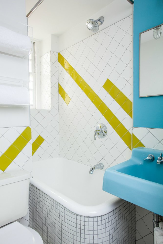 A geographic lime-green tile pattern was incorporated into the bathroom to complement the sink, which was found in an architectural salvage yard and retains its original color. Photo by Alan Gastelum. Tagged: Bath Room, Vessel Sink, Freestanding Tub, Ceramic Tile Wall, Open Shower, and Two Piece Toilet.  Photo 5 of 8 in A Gut Renovation Transforms a Tiny Manhattan Apartment