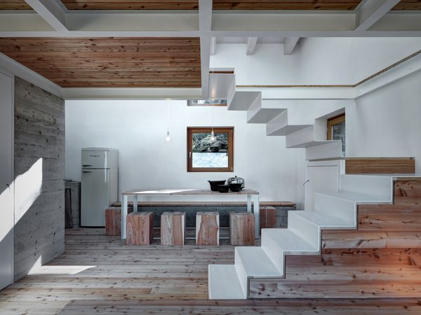 The ground floor is comprised of a living room, kitchen, and bathroom that are all detailed with larch wood. In the kitchen, a retro Bompani refrigerator and freezer blend in with the minimal aesthetic.