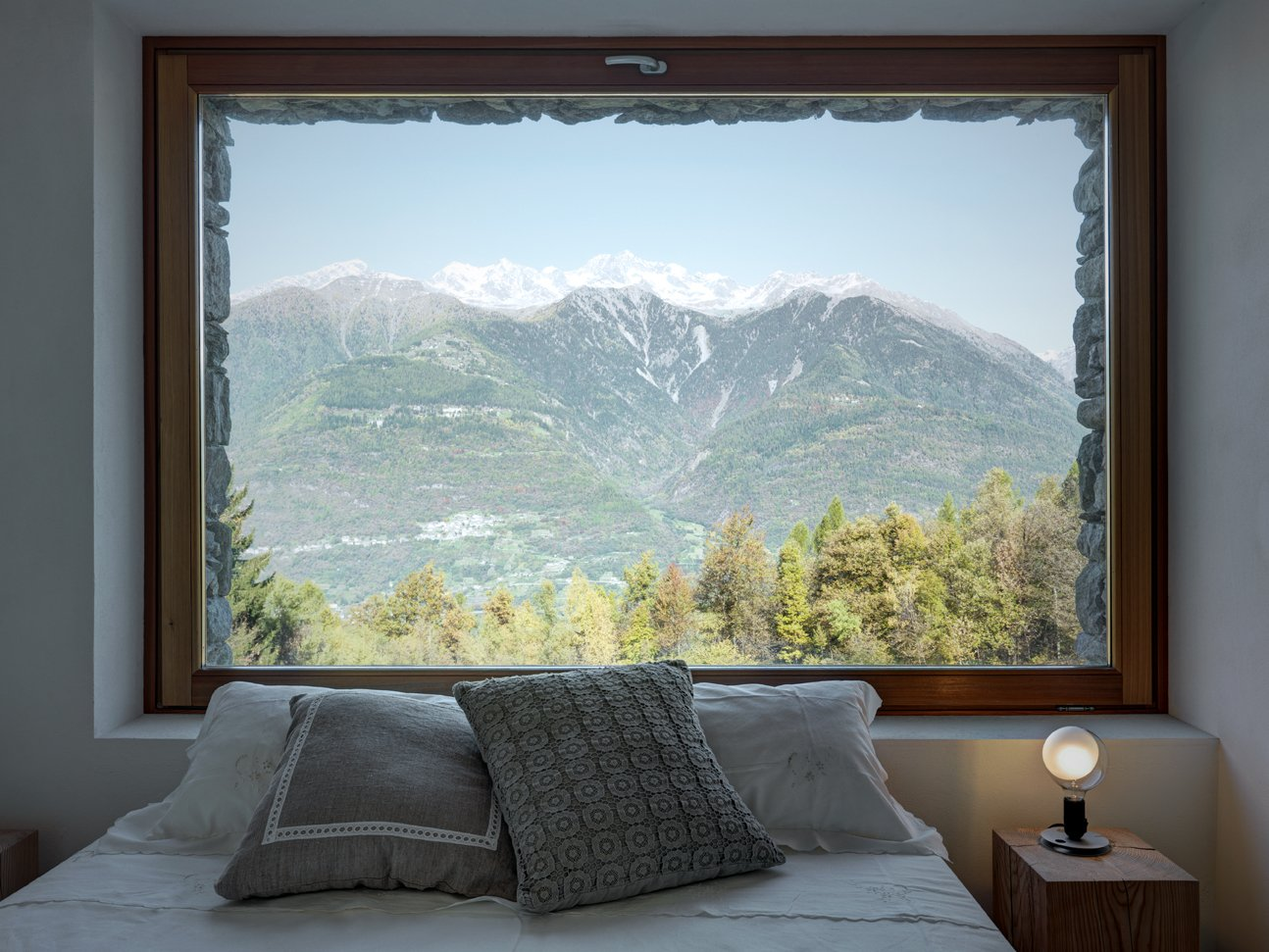 Views of the Orobie Alps can be seen from the home's windows, which also feature larch frames. A lampadina light by Flos sits on the nightstand. Tagged: Windows and Picture Window Type.  Modern Winter Retreats by Aileen Kwun from A Stunning Alpine Home with Sweeping Views and Custom Crafted Interior