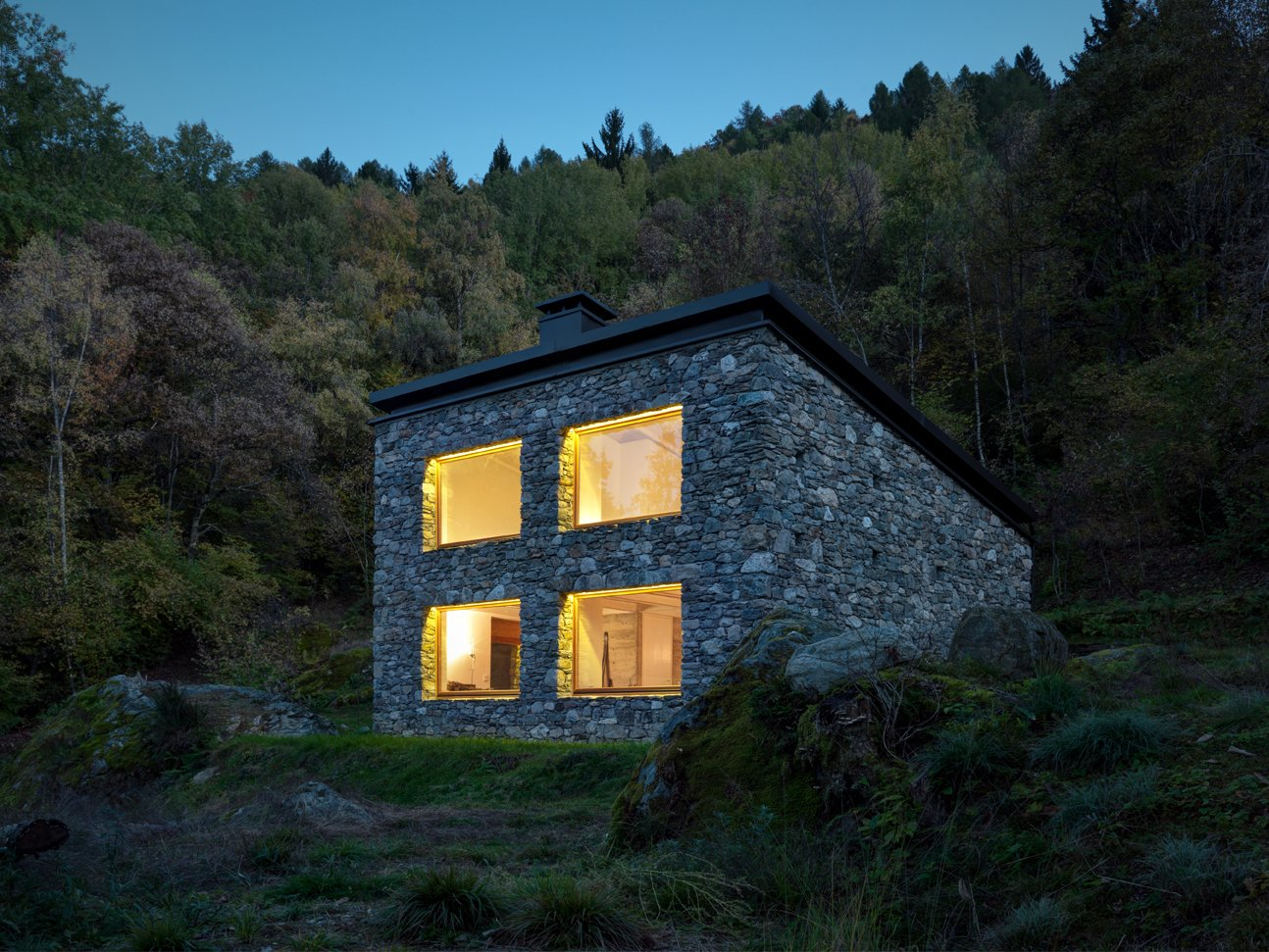 """The positioning of the home's roof allowed for a double-height, north-facing wall with four matching windows and an accompanying skylight. """"The house refers to rural houses: a sloping roof, completely coated by stone and with no eaves,"""" Vanotti says."""