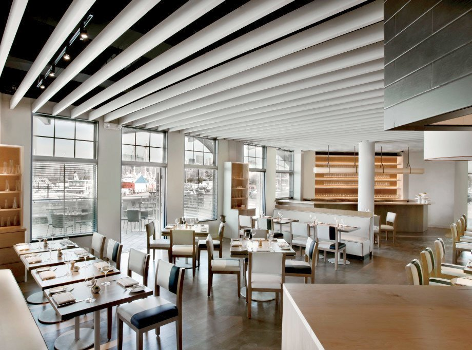 "Project: Maritime Parc, Jersey City  Stephanie Goto approaches restaurant design as a dining landscape that supports the chef's vision—even details as small as divots on a plate can ""signify an opportunity for an activity,"" she says. At Maritime Parc, her blue-gray palette complements the seafood-centric menu, while a slatted wood ceiling calls yachts to mind. ""We design down to the tabletop,"" says Goto. ""It's about setting a stage that evokes a feeling that may be enhanced by the food and wine. The food dances with the environment.""  Designing for the Five Senses: Products to Enhance Your Palate by Allie Weiss"
