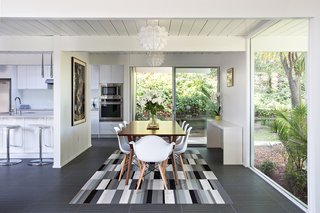 Eichler Remodel in Burlingame, California - Photo 1 of 7 - In an effort to create a more open floor plan, a portion of the wall between the kitchen, family area, and dining room was removed. Part of the dining room wall was also replaced with a huge window that not only makes a statement, but also gives the family a stunning view of the backyard area. Photo by Mariko Reed.