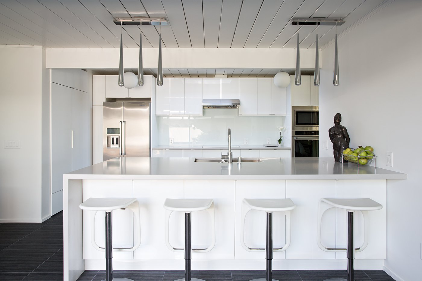 The kitchen remodel included creating more space and installing a single-plane island that served as the perfect spot for the family's children to do everything from eating to studying schoolwork. Photo by Mariko Reed. Tagged: Kitchen, White Cabinet, and Pendant Lighting.  Modern Eichler Renovations by Allie Weiss from Eichler Remodel in Burlingame, California