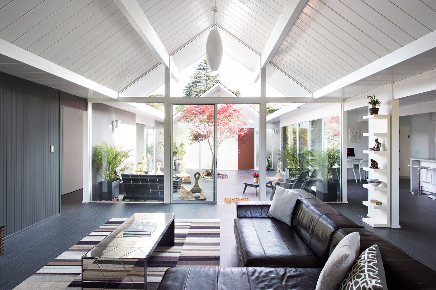 Here, the relationship between indoors and outdoors is on full display. The architects aimed to create a smooth transition between the two areas by incorporating glass doors that don't obstruct any views. Photo by Mariko Reed.  Modern Eichler Renovations by Allie Weiss from Eichler Remodel in Burlingame, California