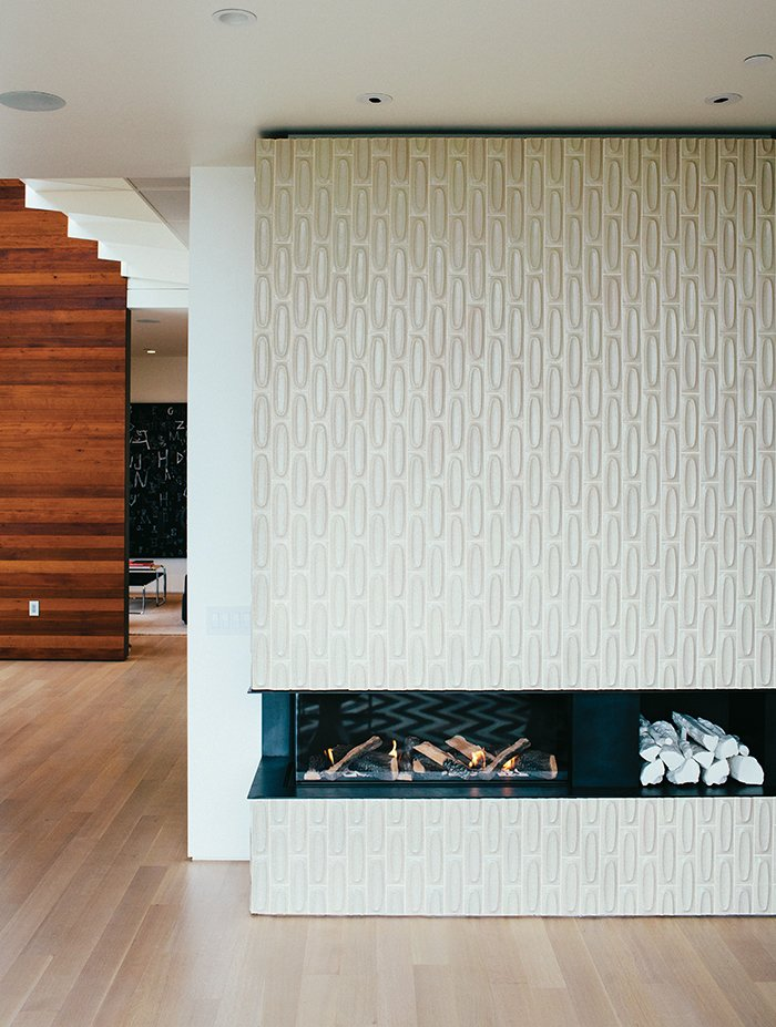Tiles from Heath Ceramics surround the new, low-slung fireplace. The white ceramic logs are by Klein Reid; the floor is oak.