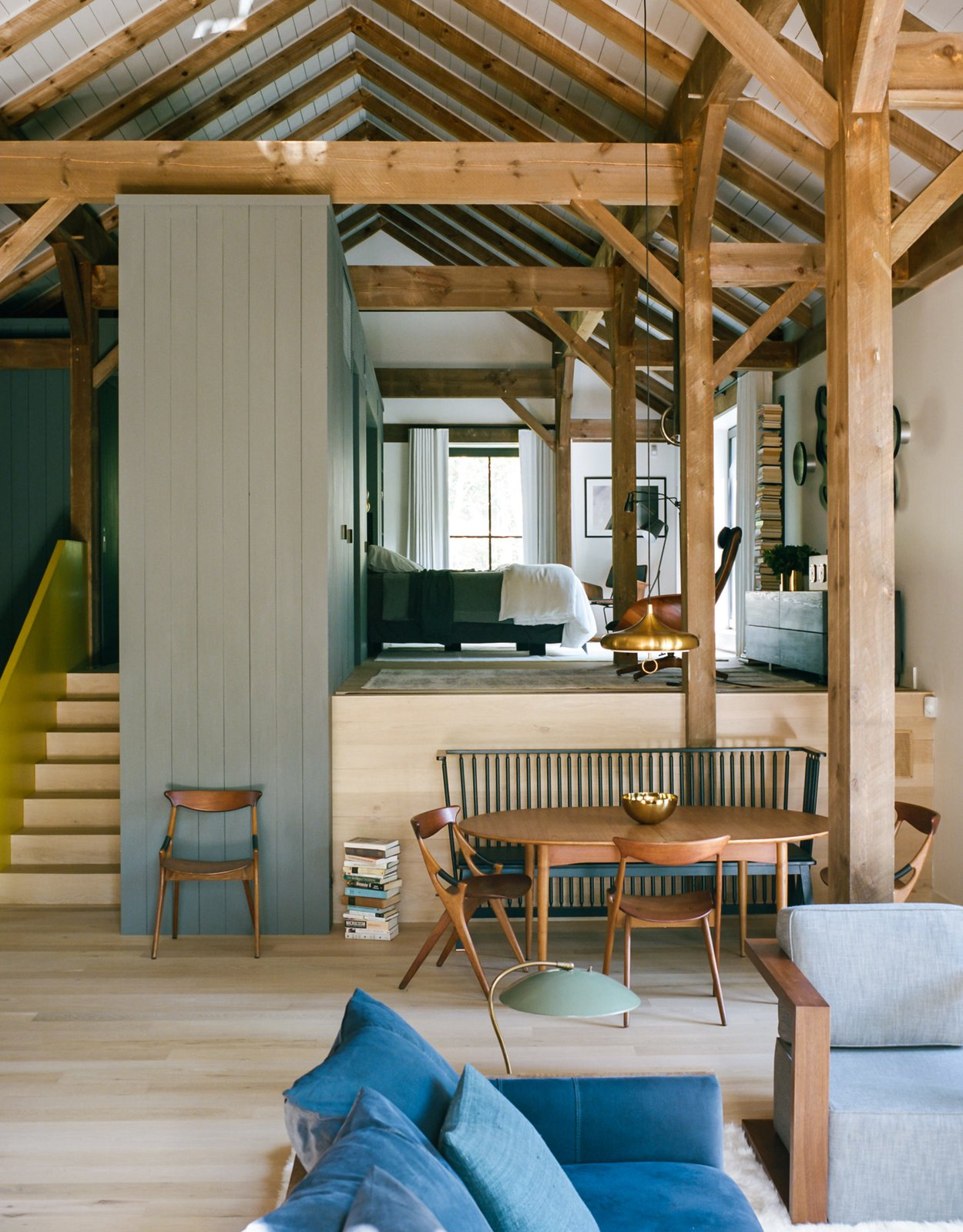 """The open living-and-bedroom area of Ian Hague's rural retreat can be divided by a wall that rises from within the master-suite platform. Interior designer Elaine Santos blended her client's collection of vintage furniture with no-fuss pieces like a Shaker-style bench by Ilse Crawford for De La Espada. Tagged: Living Room, Chair, Sofa, Table, and Light Hardwood Floor.  Colorful Intentions by Meg Dwyer from A Passive House and """"Sauna Tower"""" Join a 19th-Century Barn in the Hudson Valley"""