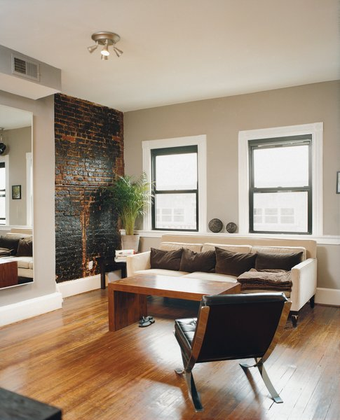 Peeling back plaster and drywall they unearthed beautiful brick walls. They opted to leave them exposed, letting light from the street and a wall of rough-hewn red brick warm up the large living rooms and kitchens. Mazza's living room sofa is from Crate and Barrel.