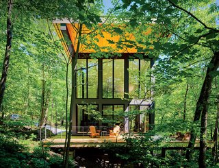 "101 Best Modern Cabins - Photo 36 of 101 - A cantilevered cabin designed by R D Gentzler blends into the forest, even as it hovers above a 20-foot drop-off. Its south face is almost entirely glass, but a roof canopy limits solar gain. ""We sit on the deck all afternoon watching the trees, and the time just flies by,"" says resident Maricela Salas."