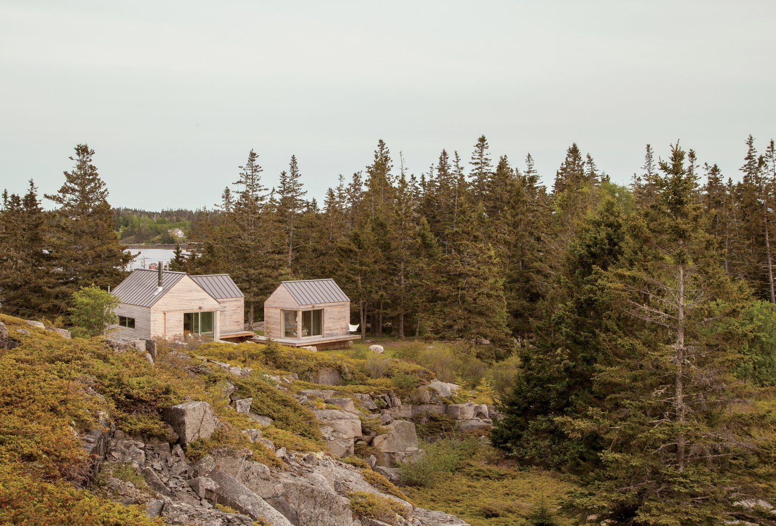 On a sloping site near a defunct rock quarry on the remote lobster-fishing island of Vinalhaven, Maine, a three-part summer home overlooks a framed view of Penobscot Bay. Working around the site's unique topography, design-build firm GO Logic created each structure at varying elevations. Tagged: Exterior, Cabin Building Type, Shingles Roof Material, and Wood Siding Material.  Photo 9 of 101 in 101 Best Modern Cabins from A Cluster of Cabins in a Former Quarry Makes a Simple Vacation Escape