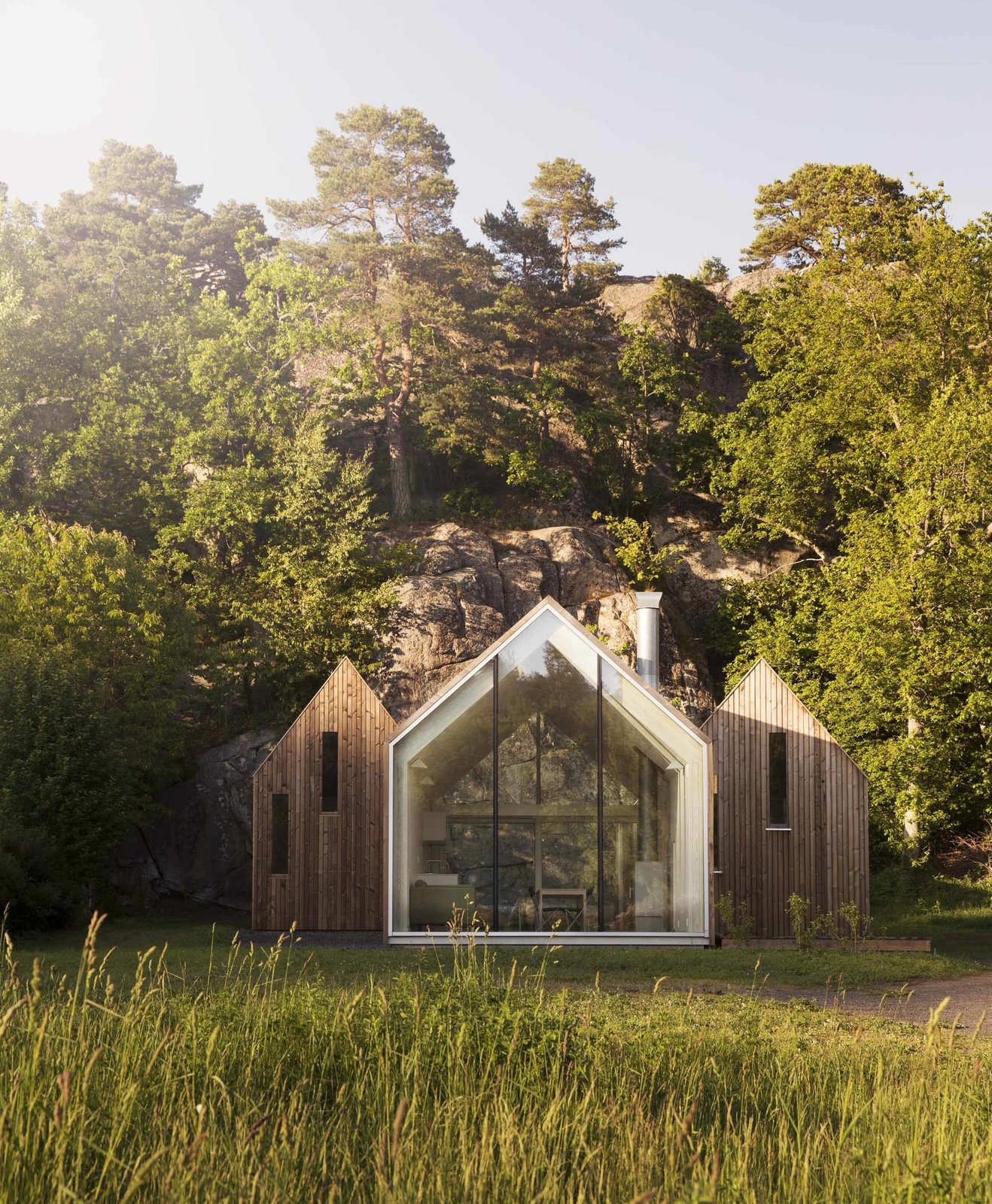The family retreat abuts a rocky cliff in Herfell, Norway. The central cabin provides communal living spaces, while the two cabins that flank it are used as private sleeping quarters. Tagged: Exterior, Cabin Building Type, and Wood Siding Material.  Photo 49 of 101 in 101 Best Modern Cabins from Little Homes in the Country