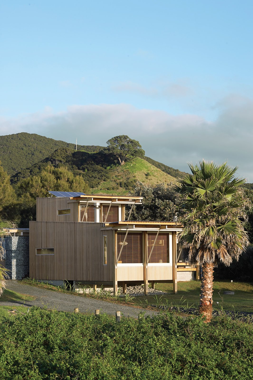 The cedar-clad home designed by Herbst Architects faces the Pacific Ocean, tucked behind sand dunes from the sparsely populated Medlands Beach. Tagged: Exterior, House, Wood Siding Material, and Flat RoofLine.  Best Photos from New Zealand Vacation Home Designed Completely Off the Grid