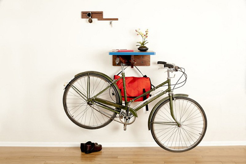 Board By Design's handmade shelf lets you hang your bike by its saddle, handling any and all bike shapes and sizes. Your bike will look as if its floating elegantly by the wall. Better yet, The Bike All shelf has two hooks for your helmet and bag. Place your smaller belongings on the top shelf—there's even an opening for your cell phone charger. The all-wood unit is especially handy for the space-deprived, measuring in at only 20-inches long and 7-inches tall.   Photo by: BBD  Storage by Dwell from Shelf Aware: 10 Wall-Mounted Storage Solutions We Love