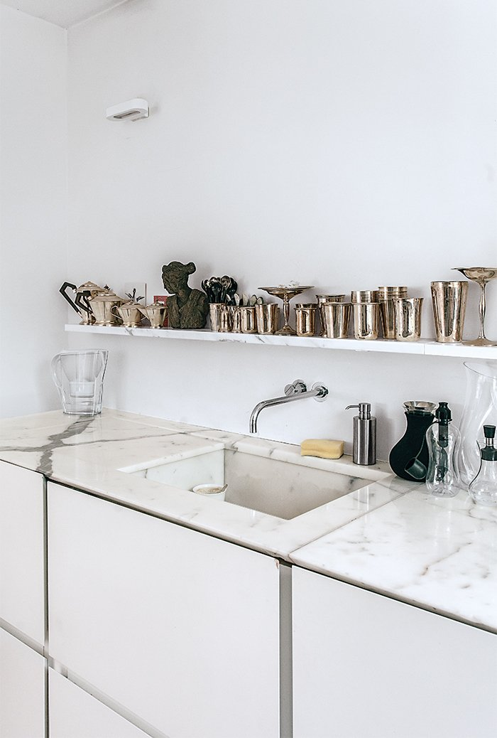 Molineus designed all of the storage units in the apartment, including the lacquered medium-density fiberboard cabinets under the kitchen sink, which is outfitted with a Vola faucet. Tagged: Kitchen, Marble Counter, Undermount Sink, Wall Lighting, Open Cabinet, and White Cabinet.  Photo 10 of 21 in Mad About Marble: 20 Kitchens and Bathrooms from An American Ex-Pat Renovates a Tiny London Apartment on Her Own Terms