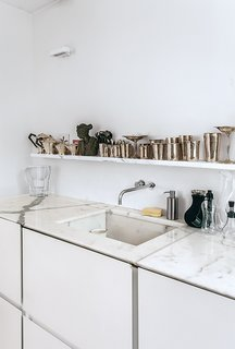 Mad About Marble: 20 Kitchens and Bathrooms - Photo 9 of 20 - Molineus designed all of the storage units in the apartment, including the lacquered medium-density fiberboard cabinets under the kitchen sink, which is outfitted with a Vola faucet.
