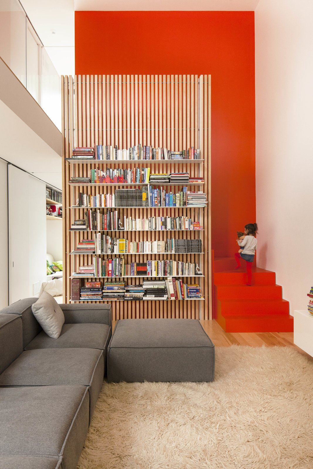 The stairs are partically hidden behind a slatted ash screen that supports steel bookshelves. Tagged: Living Room, Sectional, and Bookcase.  190+ Best Modern Staircase Ideas by Dwell from A Transformative Duplex Renovation in Montreal