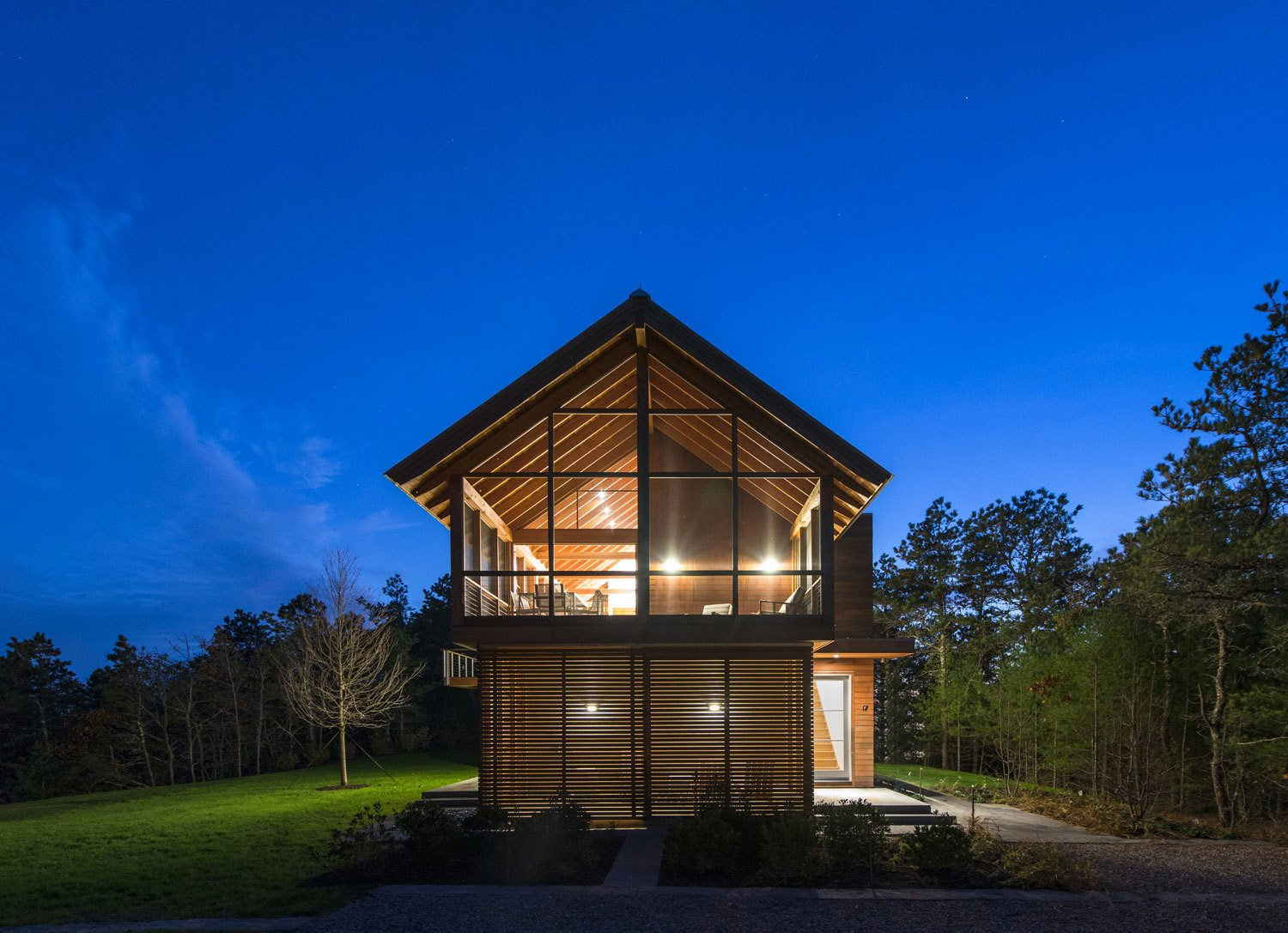 At night, the interior lighting casts the geometric window framing in silhouette. Tagged: Exterior, Cabin Building Type, Wood Siding Material, House, and Glass Siding Material.  Photo 37 of 101 in 101 Best Modern Cabins from Modern Gabled Cabins