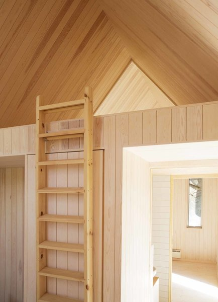 The auxiliary cabins contain the sleeping quarters. A ladder leads to a sleeping loft underneath a gabled ceiling. The cabin's bathroom is situated beneath the loft and features clean white fittings and tile.