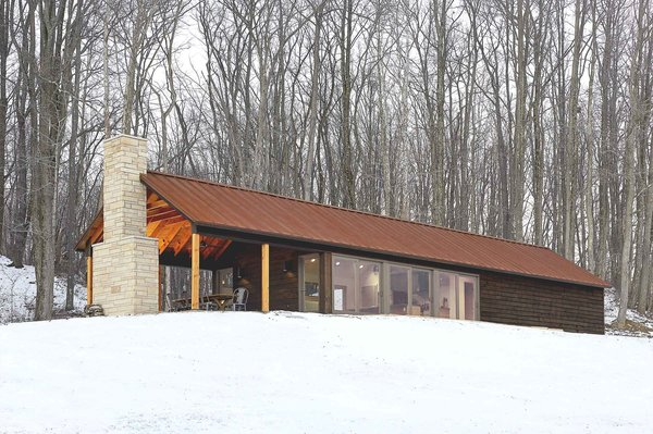 The retreat's southern exposure maximizes sunlight with 24 feet of floor-to-ceiling windows. The sun's warmth is absorbed and stored in the concrete floor, keeping the interior warm. Combined with thickly insulated walls, the cabin requires little additional energy, and has gone up to three days in winter without any electrical heating. Photo 3 of Off-Grid Retreat modern home