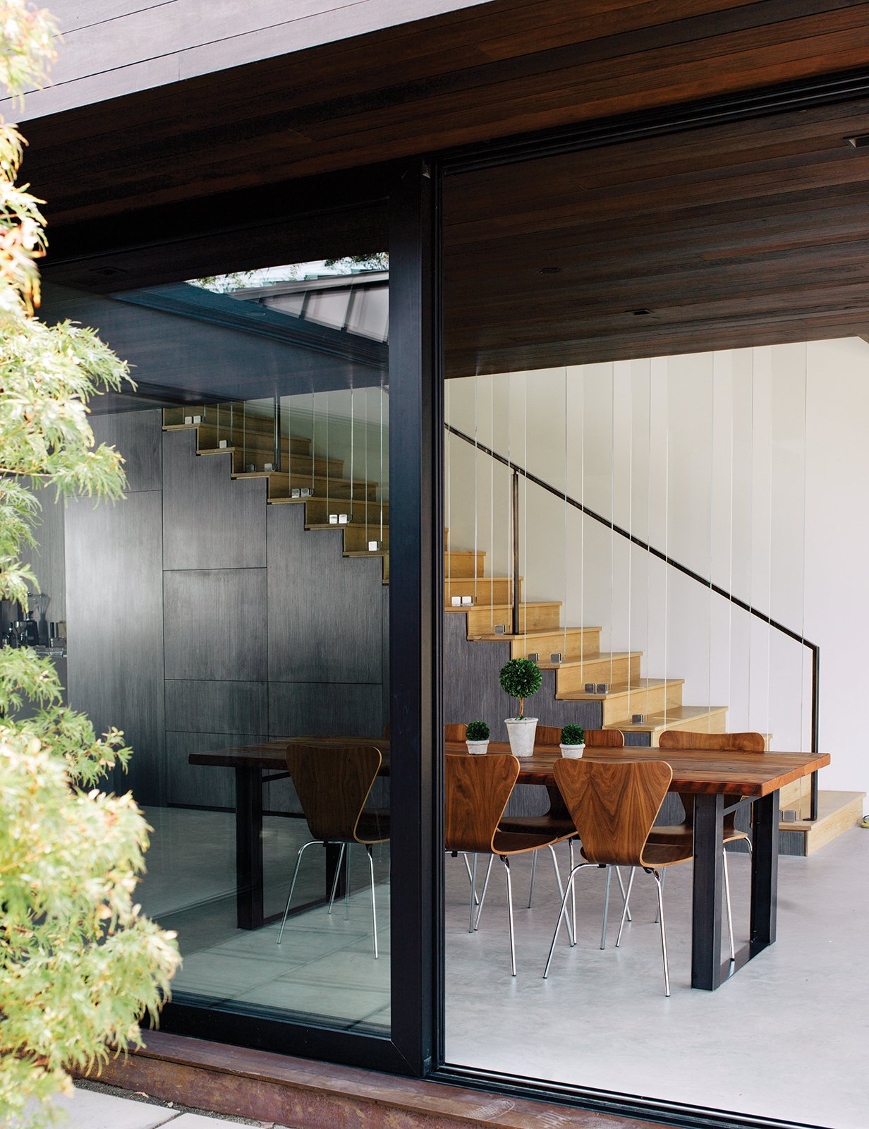 """The new volume houses the dining area, which includes stairs to the bedrooms. The table is from Blake Avenue and the walnut chairs are from Room & Board. """"You don't want bright colors to take away from that relationship between the interior and the exterior,"""" Walker says.  Photo 4 of 10 in Modern Home Designed for Live Music in Beverly Hills"""